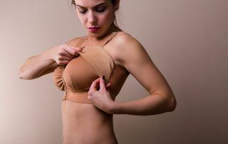 breast augmentation recovery featured image with woman putting on compression bra